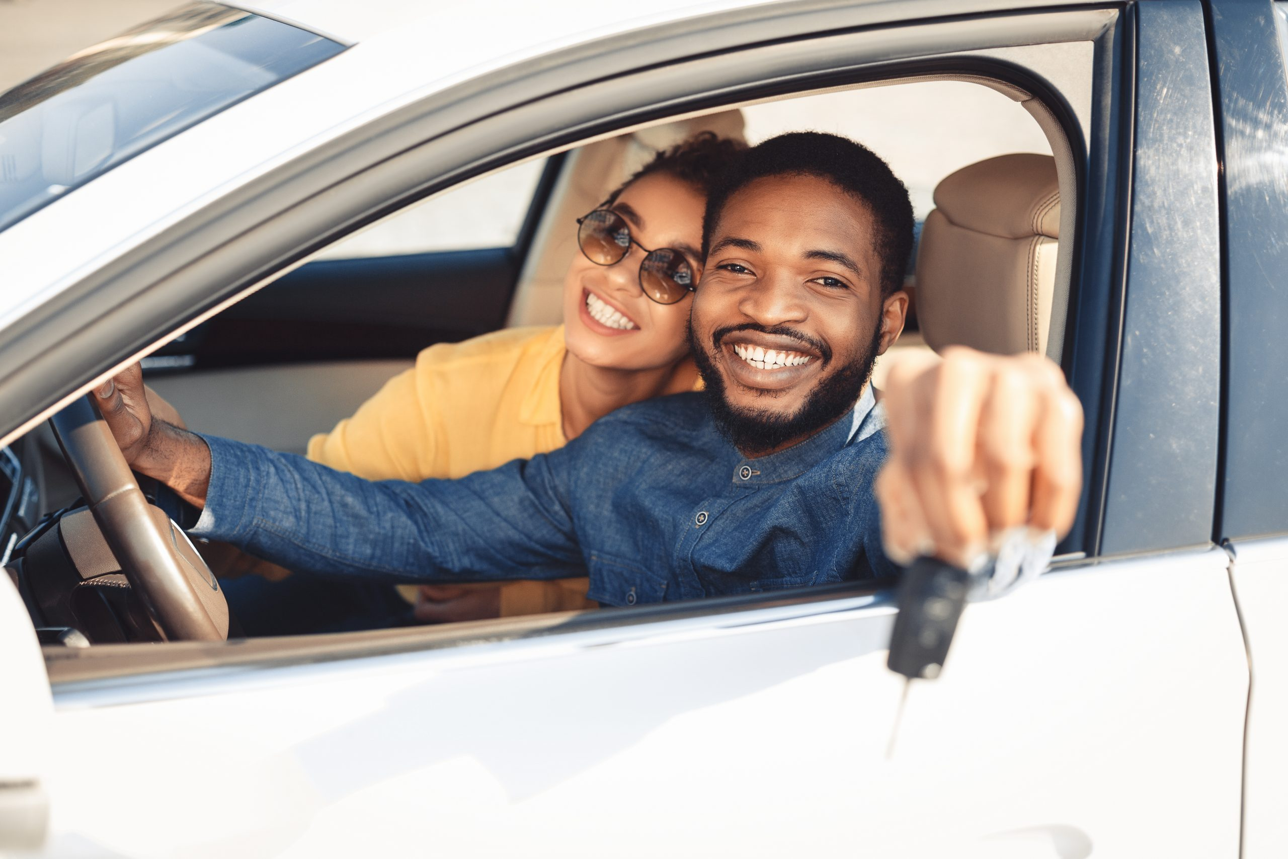 Couple sitting in new car holding keys out the window after buying new car