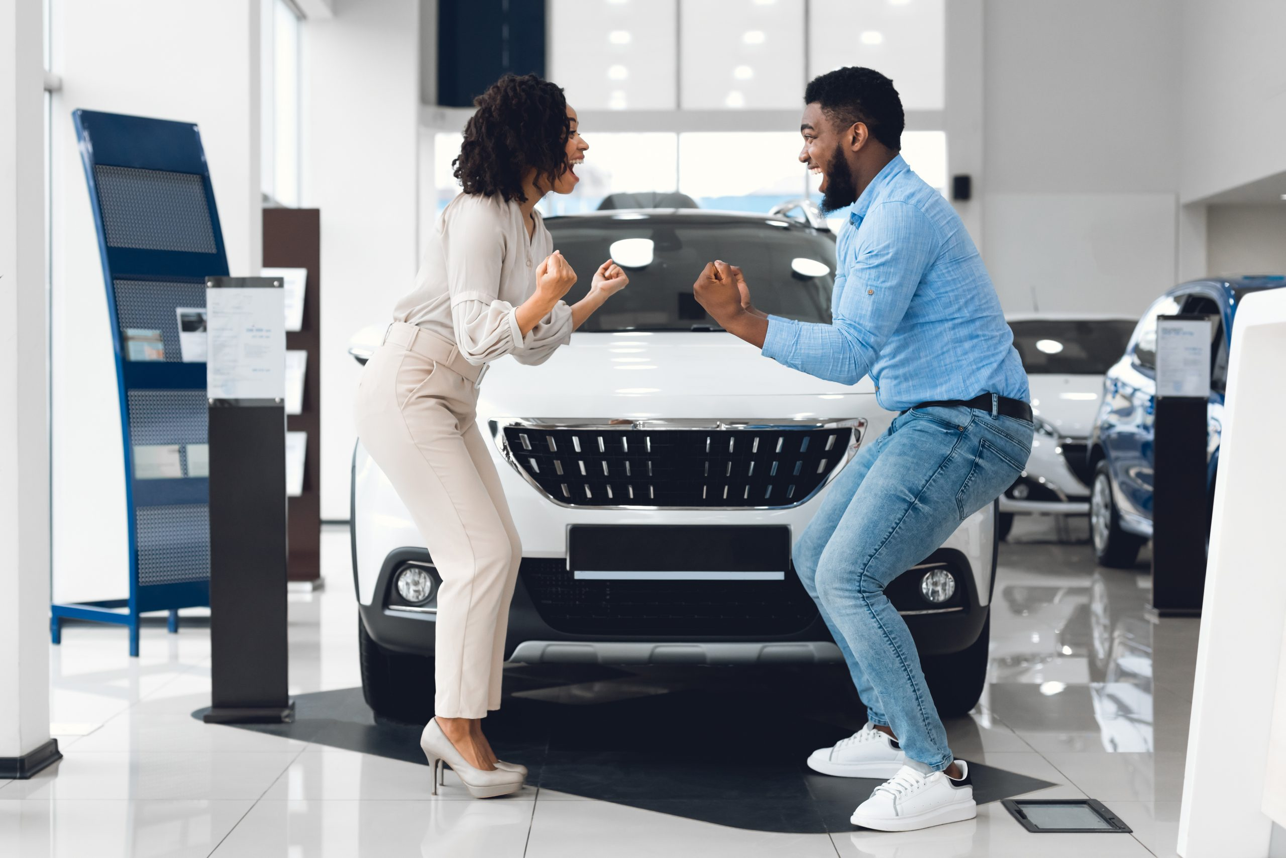 Excited couple in a car showroom excited is it better to lease or buy a car
