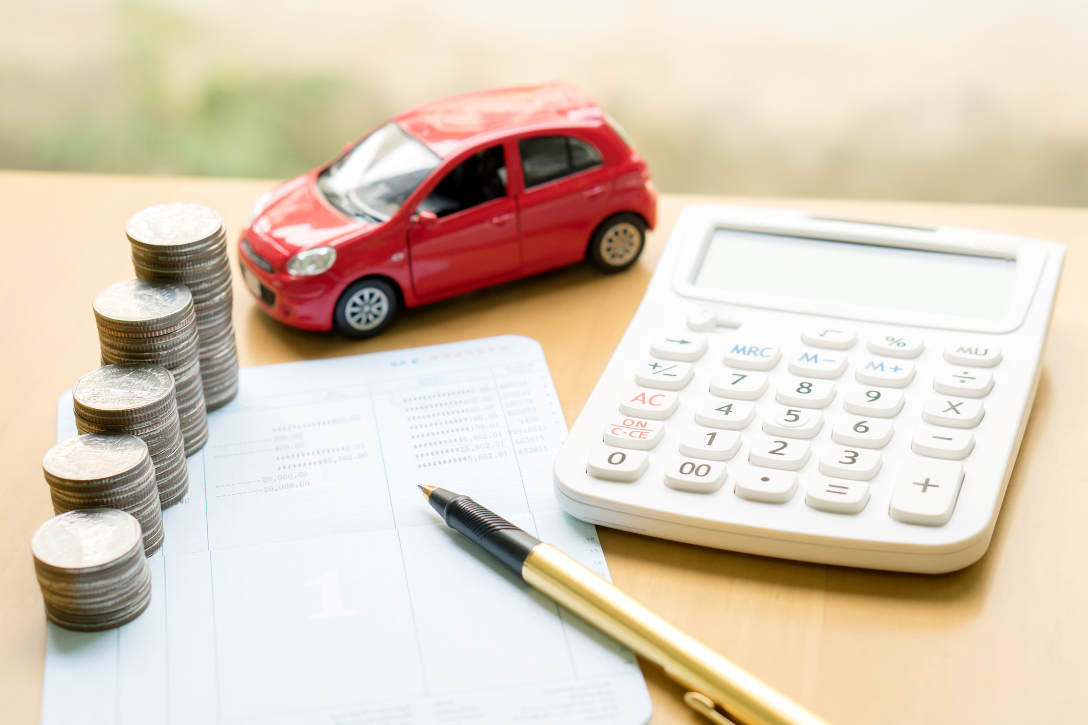 Coins stack in columns on saving book and car on finance concept